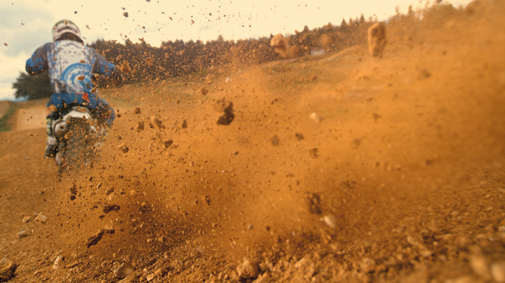 Motocross rider riding on dirt track.