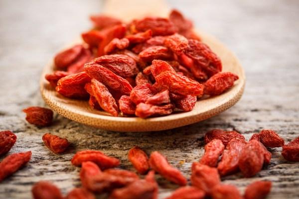 Red dried goji berries in wooden spoon