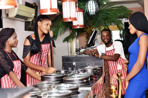3 women and 1 man standing around pots and pans in the kitchen depicting a small catering business in Nigeria.