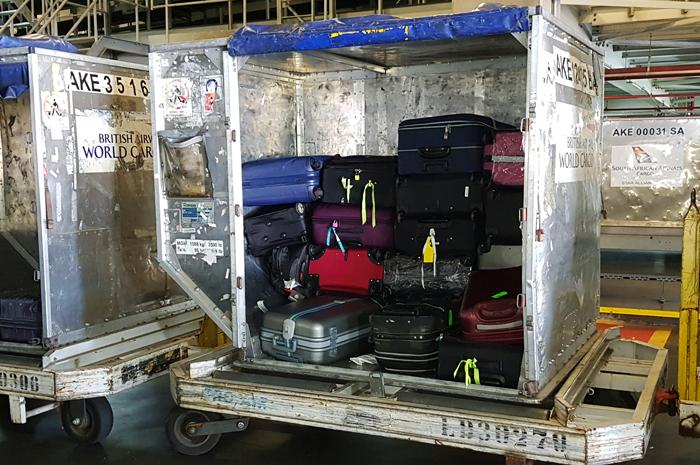 Contêineres carregados com malas dos passageiros