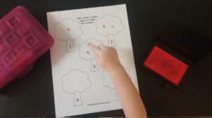 Preschooler making fingerprint apples on tree