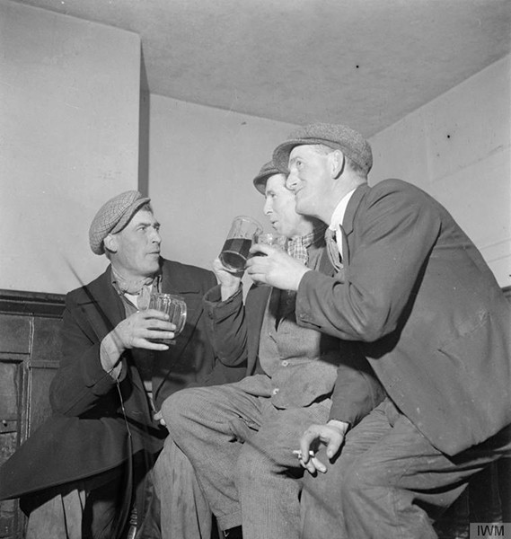 Three men discuss various local issues over a pint of beer and a cigarette at the Wynnstay Arms in Ruabon, Denbighshire, Wales. From the Ministry of Information Second World War Collection, Imperial War Museum. © IWM (D 18478)
