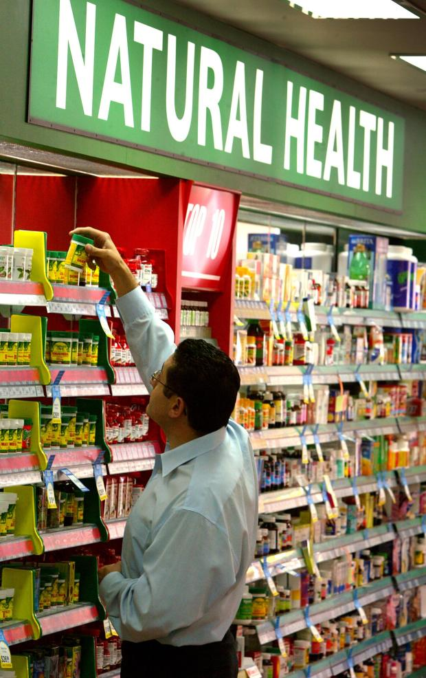 A store worker checks the brand names of rows of herbal, vitamin and mineral pillls at a pharmacy.