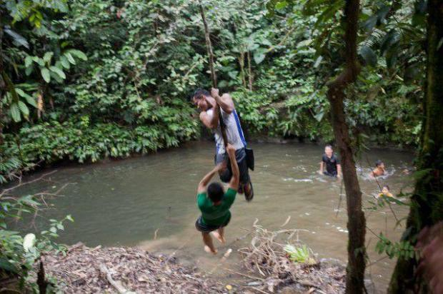 Ecuadorean boys play in a shallow swimming hole near Yawepare, Ecuador. The country's push to drill for oil is threatening Amazon forests and pitting native tribes against each other.