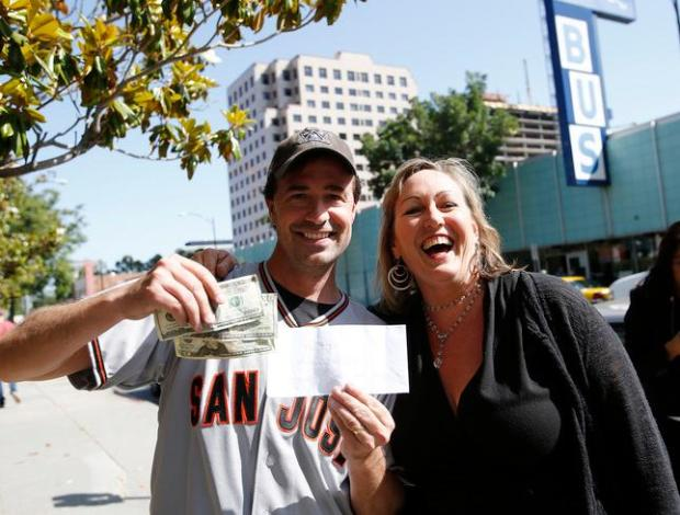 Jeff Pope and Marla Davies represent a camera shy fellow employee who found the $140 cash during a @HiddenCash treasure hunt in San Jose, Calif. on Wednesday, May 28, 2014. The money was found across the street from the Greyhound Bus station in downtown San Jose. All three of these people work down the street for the radio station, MIX 106.5. (Gary Reyes/Bay Area News Group)