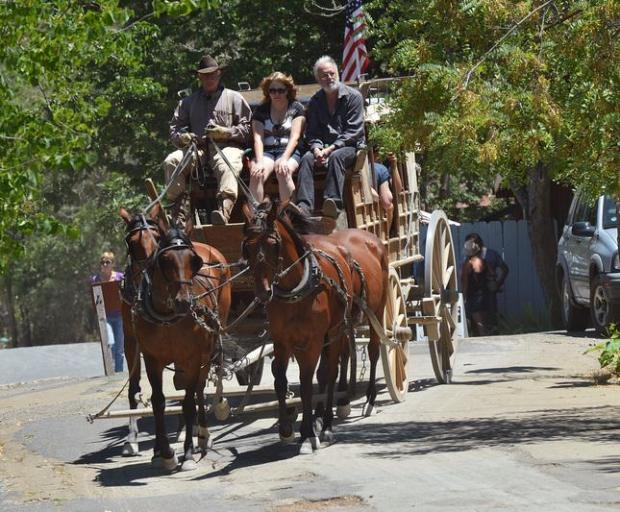 A stagecoach rounds a corner onto Main Street full of riders in Columbia State Historic Park in Columbia, Calif., on Saturday, July 12, 2014.