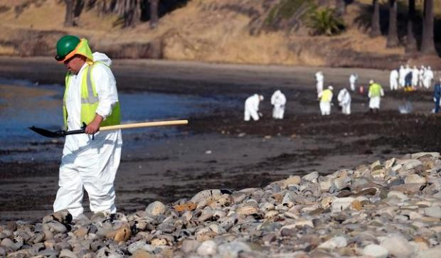 A clean up worker heads to the shoreline while a larger group of workers begin clean up operations at Refugio State Beach, site of an oil spill, north of Goleta, Calif., Wednesday, May 20, 2015. A broken onshore pipeline spewed oil down a storm drain and into the ocean for several hours Tuesday before it was shut off, creating a slick some 4 miles long about 20 miles west of Santa Barbara. (AP Photo/Michael A. Mariant)