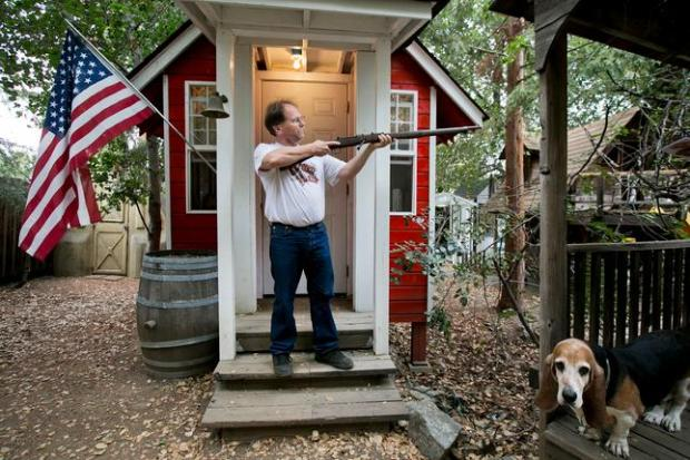 Shaughnessy McGehee poses for a portrait with a rifle from the Frontier Village in front of a scaled down replica of the Frontier Village schoolhouse that he built at his home in Campbell, Calif., on Saturday, Sept. 12, 2015. At bottom right is McGehee's dog Annie Oakley. (LiPo Ching/Bay Area News Group)