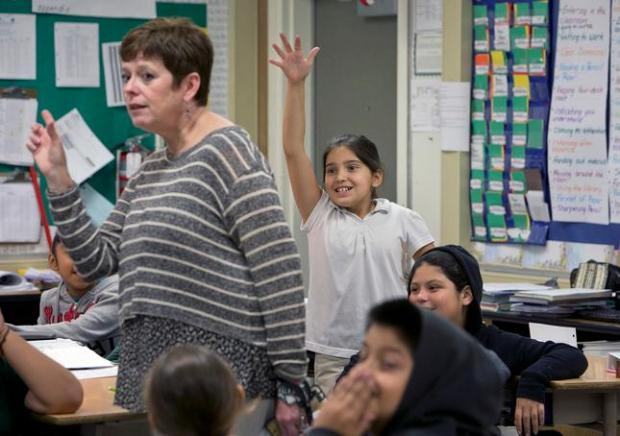 Fifth grader Jaedyn Amezcua, background, raises her hand to answer a question as Alum Rock Union Elementary School District Superintendent Hilaria Bauer, left, substitute teaches a fifth grade class at Hubbard Elementary School in San Jose, Calif., on Friday, Oct. 9, 2015. (LiPo Ching/Bay Area News Group)