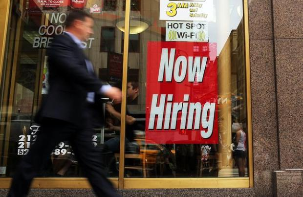 """NEW YORK, NY - AUGUST 07: A man walks by a """"now hiring"""" sign in the window of a fast food restaurant on August 7, 2012 in New York City. In a further sign that the American economy may be improving the U.S. labor Department said Tuesday that employers posted the most job openings in four years in June. The data comes after Friday's news that said employers in July added the most jobs in five months. (Photo by Spencer Platt/Getty Images)"""