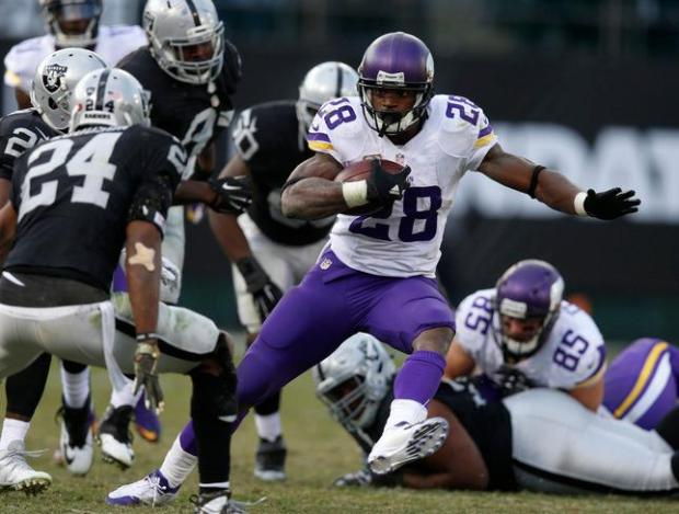 Minnesota Vikings' Adrian Peterson (28) runs against Oakland Raiders' Charles Woodson (24) in the fourth quarter of their NFL game against at O.co Coliseum in Oakland, Calif, on Sunday, Nov. 15, 2015. (Nhat V. Meyer/Bay Area News Group)