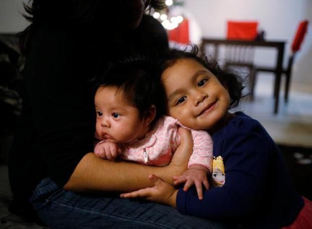 Six-week-old Brianna Saenz, is hugged by her sister Tania, 2, at their home in San Jose, Calif., on Thursday, Dec. 17, 2015. Brianna was exposed to a nurse with tuberculosis at Santa Clara Valley Medical's mother and infant care center and will have to be given daily antibiotics. (Josie Lepe/ Bay Area News Group)