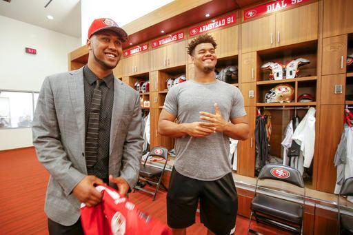 San Francisco 49ers first-round draft pick DeForest Buckner, left, from Oregon, meets with former Oregon teammate Arik Armstead, right, during an NFL football news conference in Santa Clara, Calif., Friday, April 29, 2016. (AP Photo/Tony Avelar)