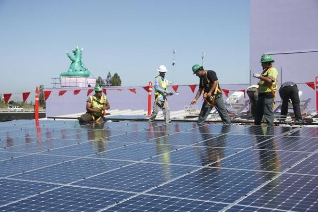 Workers install 88 solar panels atop the Children's Discovery Museum in San Jose, Calif., Thursday morning, June 30, 2016. (Karl Mondon/Bay Area News Group)