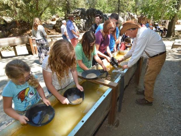 Docent Ken Valenta, right, of Columbia, teaches a family how to pan for gold at Columbia State Historic Park in Columbia. The Gold Rush town was the second biggest city in California at one point in the 19th Century. (Staff file art)
