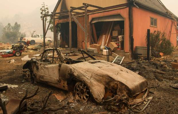 A burned out Porsche is seen near a partially burned home in the Santa Cruz Mountains near Loma Prieta, California on September 27, 2016. The Loma Prieta Fire has charred more than 1000 acres and burned multiple structures in the area. / AFP PHOTO / Josh EdelsonJOSH EDELSON/AFP/Getty Images