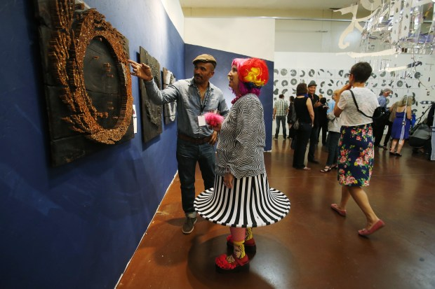 "Oakland artist Keba Konte explains his art titled ""Ring of Fire:Rust"" to Emily Duffy, of El Cerrito, during Anne & Mark's Art Party at the Santa Clara County Fairgrounds in San Jose, Calif., on Saturday, Sept. 20, 2014. Previously a private party, Anne & Mark's Art Party, started by Anne Sconberg and Mark Henderson, opened to the public for the first time. (Jim Gensheimer/Bay Area News Group)"
