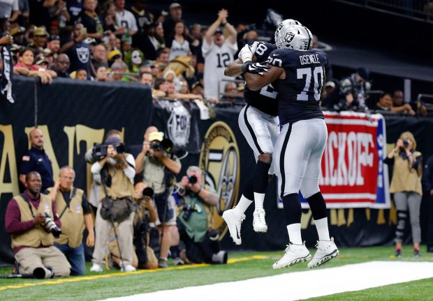 Oakland Raiders running back Latavius Murray (28) celebrates his touchdown with offensive tackle Kelechi Osemele (70) in the first half of an NFL football game in New Orleans, Sunday, Sept. 11, 2016. (AP Photo/Butch Dill)