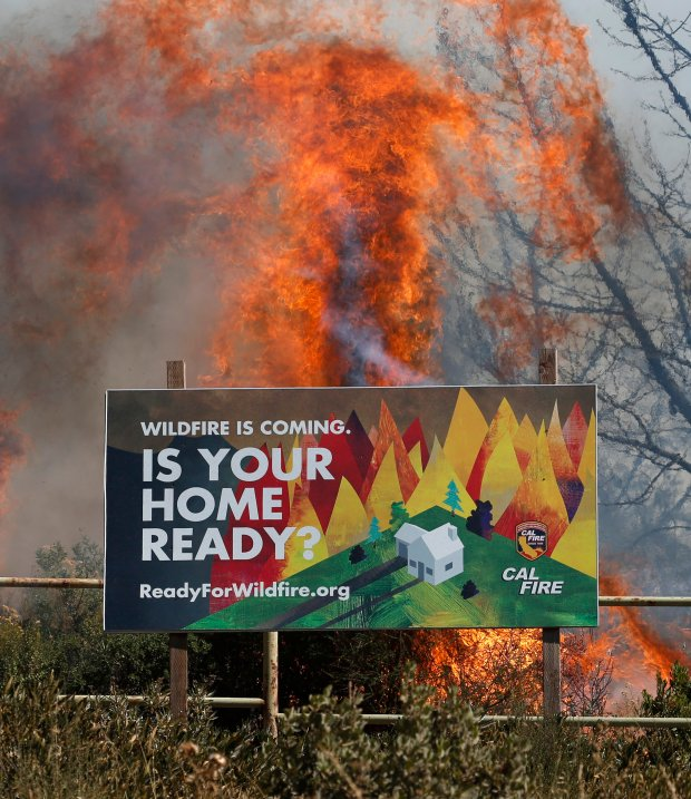 A warning sign nearly burns as firefighters work to control the Loma Fire in the Santa Cruz Mountains, 11 miles west of Morgan Hill, Calif., Tuesday, Sept. 27, 2016. The wildfire, with flames ten stories high, doubled in size overnight, burning as many as 2,000 acres in the Santa Cruz Mountains by Tuesday morning, destroying two structures and forcing hundreds to flee the area while crews from as far away as Napa rushed to contain the blaze. (Patrick Tehan/Bay Area News Group)