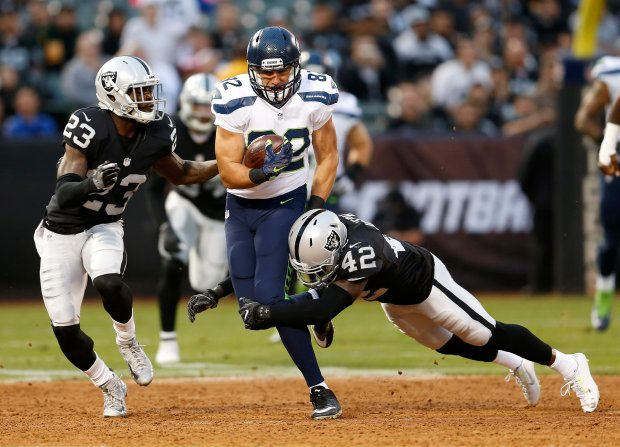 Oakland Raiders' Karl Joseph (42) tackles Seattle Seahawks' Luke Willson (82) as Raiders' Dexter McDonald (23) helps out in the first quarter of their NFL preseason game at the Coliseum in Oakland, Calif., on Thursday, Sept. 1, 2016. (Jane Tyska/Bay Area News Group)