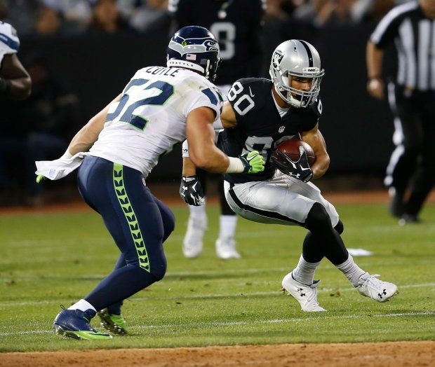 Oakland Raiders' K.J. Brent (80) carries as he's pressured by Seattle Seahawks' Brock Coyle (52)in the first quarter of their NFL preseason game at the Coliseum in Oakland, Calif., on Thursday, Sept. 1, 2016. (Jane Tyska/Bay Area News Group)