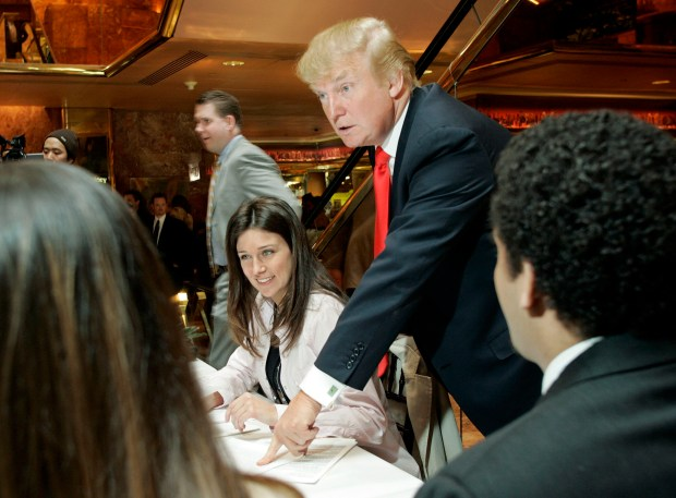 """Donald Trump speaks to hopefuls as Lauren Vaughan, a casting associate for Mark Burnett Productions, looks on, at the auditions for the sixth season of his reality television show """"The Apprentice,"""" at Trump Tower in New York, Friday, March 24, 2006. Applicants from around the country had formed a line around the block early this morning for a chance at winning eighteen spots available on the show. (AP Photo/Stuart Ramson)"""