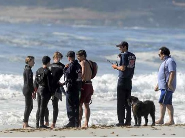Ben Weber, third from left, 17, and his friend Avery Hubbard, left, 15, speak to firefighters and a state lifeguard after Weber rescued Hubbard at Carmel Beach on Monday. (David Royal - Monterey Herald)