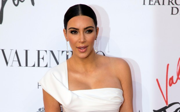 FILE - In this Sunday, May 22, 2016 file photo, Kim Kardashian poses for photographers as she arrives for the premiere of Verdi's ''La Traviata'' at the Rome Opera House, in Rome. Serial celebrity prankster Vitalii Sediuk has struck again, this time at Paris Fashion Week, targeting Kim Kardashian's derriere as she was entering the L'Avenue restaurant. Kardashian's makeup artist caught the Wednesday, Sept. 28, 2016 incident in a video that he posted to his Instagram account. It shows the reality television star negotiating her way through a crowd of paparazzi past her black car, as Sediuk, a former Ukrainian television reporter, swoops in and seems to attempt to kiss Kardashian's posterior. (AP Photo/Andrew Medichini, file)
