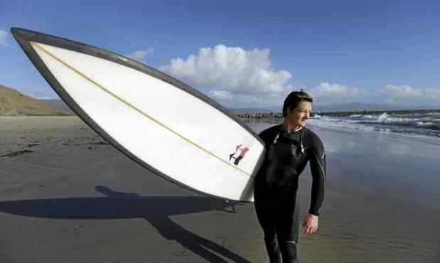 Bianca Valenti walks on the beach after surfing waves at Mavericks on Dec. 4 in Half Moon Bay. Valenti is part of the Committee for Equity in Women's Surfing, which pushed for a separate women's heat in the Titans of Mavericks competition. The group will apparently get its way this season after contest organizers announced a six-woman heat for 2016-17. Ben Margot — The Associated Press