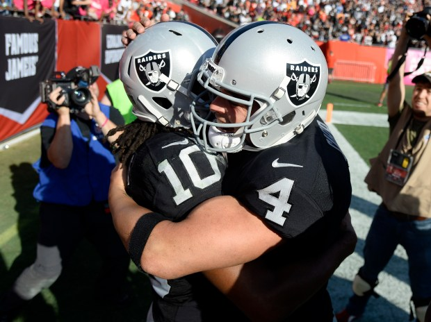 Oakland Raiders quarterback Derek Carr (4) hugs wide receiver Seth Roberts (10) after Roberts scored on a 41-yard touchdown reception from Carr during overtime in an NFL football game Sunday, Oct. 30, 2016, in Tampa, Fla. The Raiders won the game 30-24. (AP Photo/Jason Behnken)