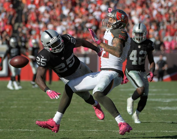 Oakland Raiders cornerback D.J. Hayden (25) breaks up a pass intended for Tampa Bay Buccaneers wide receiver Mike Evans (13) during overtime in an NFL football game Sunday, Oct. 30, 2016, in Tampa, Fla. (AP Photo/Phelan Ebenhack)