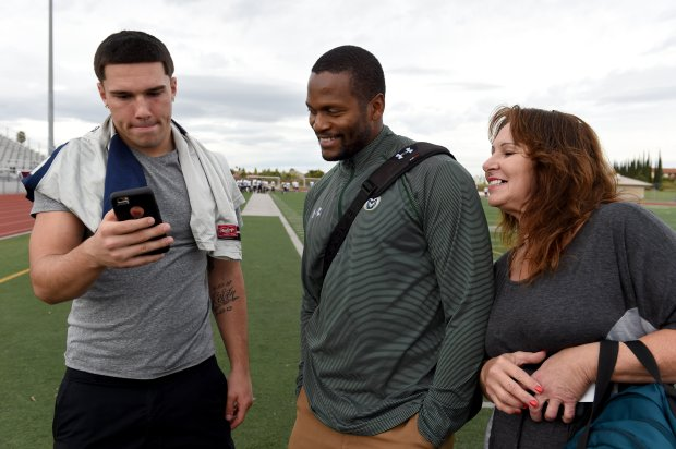 Freedom High linebacker Kyle Harmon,17, left, watches a cell phone video of his last game with Alvis Whitted, from Colorado State University recruiting and his mother Cherri Harmon at Freedom in Oakley, Calif., on Monday, Oct. 24, 2016. Harmon has gotten offers to play for fifteen colleges thus far. (Susan Tripp Pollard/Bay Area News Group)