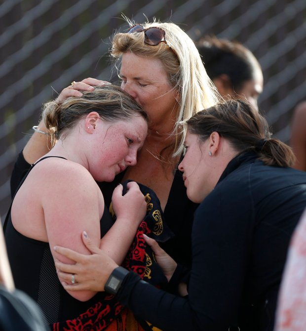 Audrey Benton, left, is comforted by her mother Sarah Thompson, center, and coach Melissa Shimer, right, after a water polo game at Fairfield High School on Thursday, Oct. 13, 2016, in Fairfield, Calif. Benton suffered a stroke after being bitten by a snake during a summer trip to Belize. (Aric Crabb/Bay Area News Group)