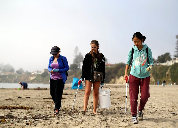 Kirby students Sonja Fauske, from left, Emma Nelson and Jackie Zhao pick up pieces of garbage as they walk along Cowell Beach in Santa Cruz on Saturday morning where Save Our Shores hosted the annual Coastal Cleanup event. (Kevin Johnson -- Santa Cruz Sentinel)