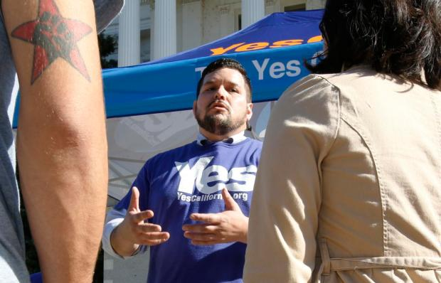 Marcus Ruiz Evans, center, of The Yes California Independence Campaign, talks to passersby about California succeeding from the United States and becoming its own nation, Wednesday, Nov. 9, 2016, in Sacramento, Calif., . Support for the proposal grew on social media following Tuesday's election of Republican Donald Trump. (AP Photo/Rich Pedroncelli)