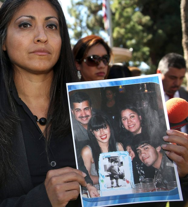 2014: Attorney Claudia Osuna holds a photo of the Crespo family - Bell Gardens, Calif., Mayor Daniel Crespo, his daughter Crystal, his wife Lyvette and son Daniel Crespo Jr. (AP Photo/Nick Ut, File)