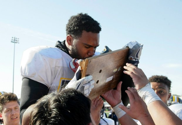 Lincoln High linebacker Adrian frometa #52 gives the Big Bone trophy a kiss after the annual Big Bone game played at Independence High School on November 24, 2016 in San Jose, California. With a final score of 41-13, Lincoln High School defeated San Jose High School for the 19th consecutive time. (Photo by John Medina for SVCN)