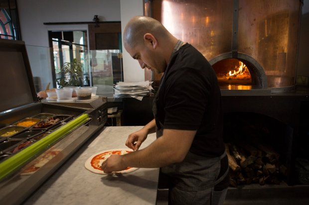 Chef Genaro Mendez makes a pizza at the Creek Eatery in San Jose, Calif., Tuesday, Nov. 22, 2016. (Patrick Tehan/Bay Area News Group)