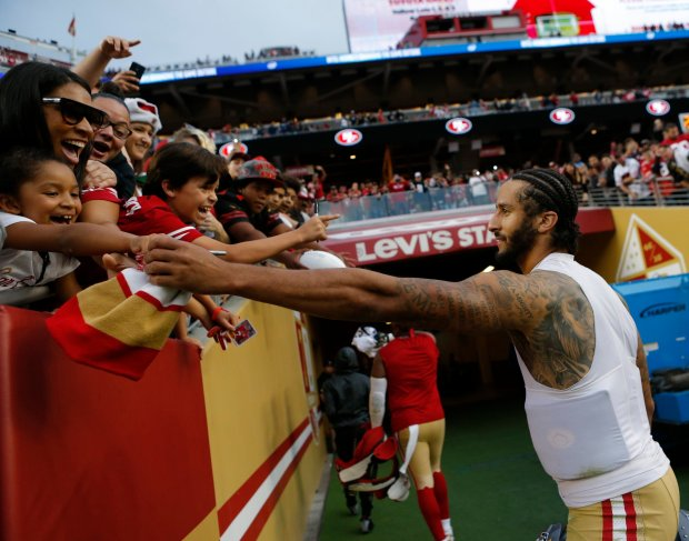 San Francisco 49ers quarterback Colin Kaepernick gives his 49ers beanie to Taylor Damor after Sunday's game.