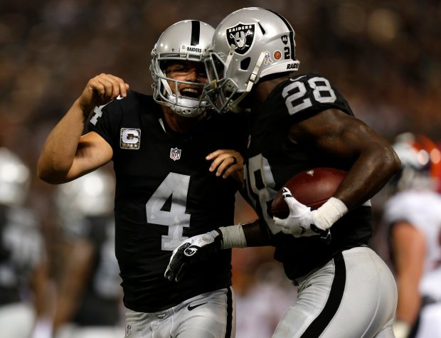 Oakland Raiders quarterback Derek Carr (4) celebrates a touchdown by Oakland Raiders' Latavius Murray (28) in the second quarter of their NFL game against the Denver Broncos at the Coliseum in Oakland, Calif., on Sunday, Nov. 6, 2016. (Nhat V. Meyer/Bay Area News Group)
