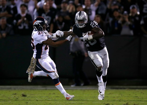 Oakland Raiders' Latavius Murray (28) runs against Denver Broncos' Chris Harris Jr. (25) in the fourth quarter of their NFL game at the Coliseum in Oakland, Calif., on Sunday, Nov. 6, 2016. (Nhat V. Meyer/Bay Area News Group)