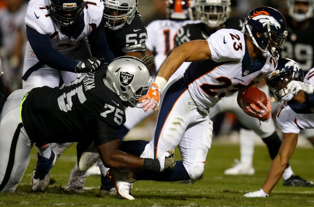 Oakland Raiders' Darius Latham (75) tackles Denver Broncos' Devontae Booker (23) in the second quarter of their NFL game at the Coliseum in Oakland, Calif., on Sunday, Nov. 6, 2016. (Nhat V. Meyer/Bay Area News Group)