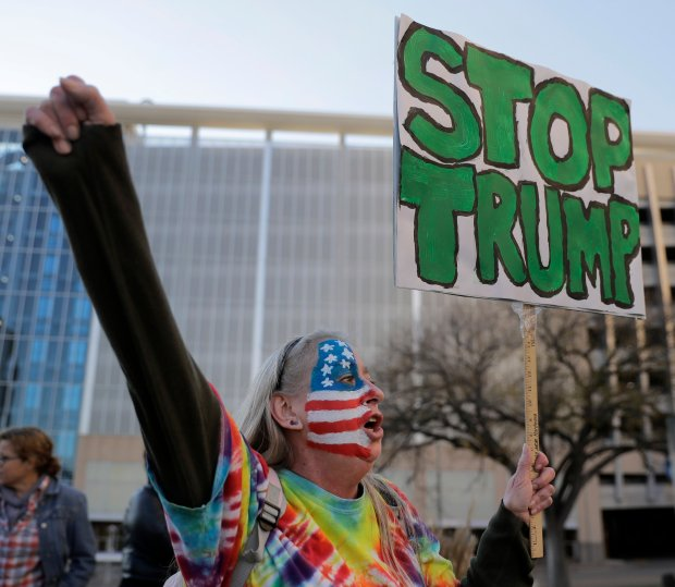 Mary Johnson protests against the election of President-elect Donald Trump Saturday, Nov. 12, 2016, in front of City Hall in Kansas City, Mo. (AP Photo/Charlie Riedel)