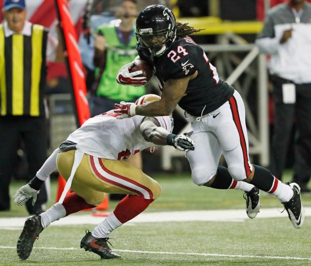 Atlanta Falcons running back Devonta Freeman (24) runs past San Francisco 49ers free safety Jaquiski Tartt (29) during the first half of an NFL football game, Sunday, Dec. 18, 2016, in Atlanta. (AP Photo/John Bazemore)