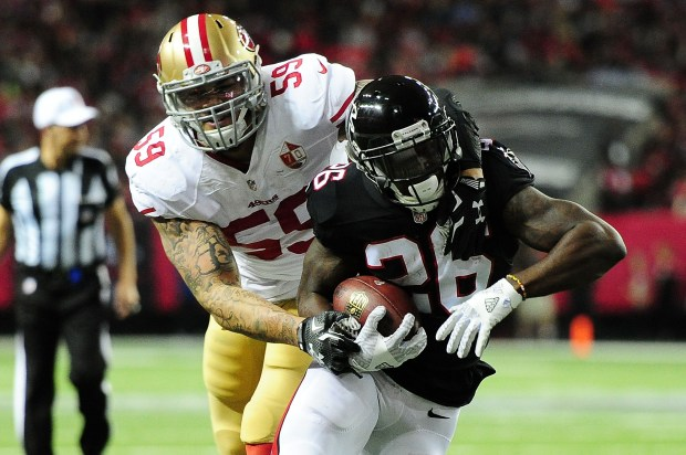 Tevin Coleman #26 of the Atlanta Falcons is tackled by Aaron Lynch #59 of the San Francisco 49ers during the first half at the Georgia Dome on December 18, 2016 in Atlanta, Georgia. (Photo by Scott Cunningham/Getty Images)