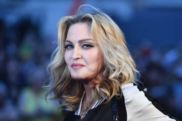 "(FILES) This file photo taken on September 15, 2016 shows US singer-songwriter Madonna poses arriving on the carpet to attend a special screening of the film ""The Beatles Eight Days A Week: The Touring Years"" in London.Madonna is voicing despair over Donald Trump's election victory and blamed women, saying they had a ""tribal inability"" to accept a female president. The election ""felt like a combination of the heartbreak and betrayal you feel when someone you love more than anything leaves you, and also a death,"" the pop icon told Billboard magazine in an interview published December 5, 2016. / AFP PHOTO / Ben STANSALLBEN STANSALL/AFP/Getty Images"