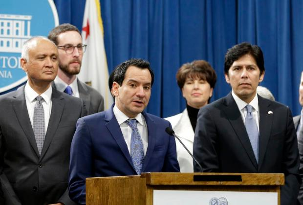 In this photo taken Monday, Dec. 5, 2016, California Assembly Speaker Anthony Rendon, D-Paramount, third from left, flanked by Senate President Pro Tem Kevin de Leon, D-Los Angeles, right, and other Democratic lawmakers, discusses a pair of proposed measures to protect immigrants during a news conference in Sacramento. (AP Photo/Rich Pedroncelli)