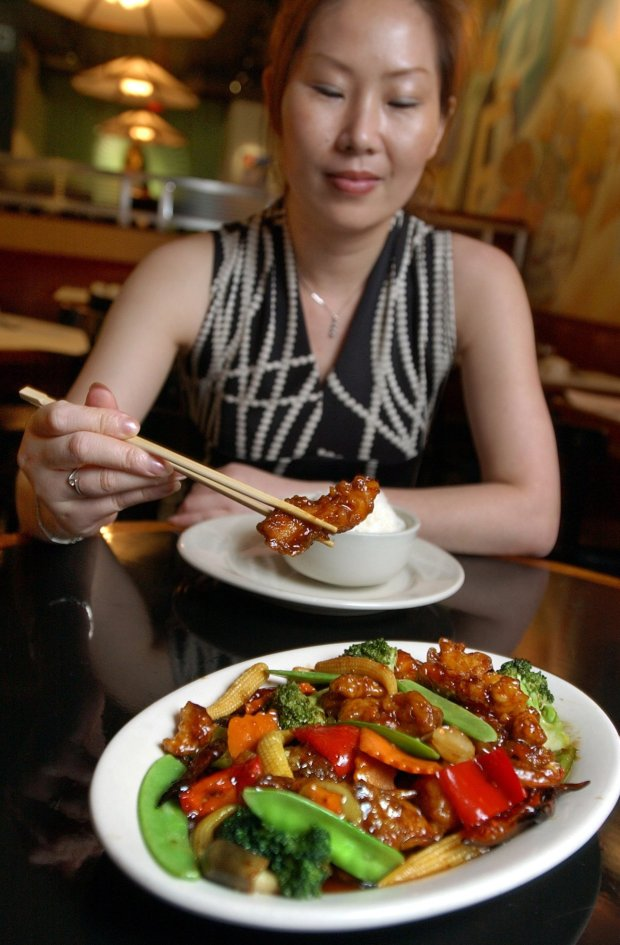 Tong Xian Mei, of Ollie's Restaurant, samples from a plate of General Tso's Chicken in New York. (AP Photo/Richard Drew, File)