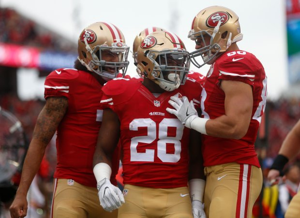 San Francisco 49ers' Carlos Hyde (28) is congratulated on his touchdown against the New York Jets in the first quarter of their NFL game at Levi's Stadium in Santa Clara, Calif., on Sunday, Dec. 11, 2016. (Nhat V. Meyer/Bay Area News Group)