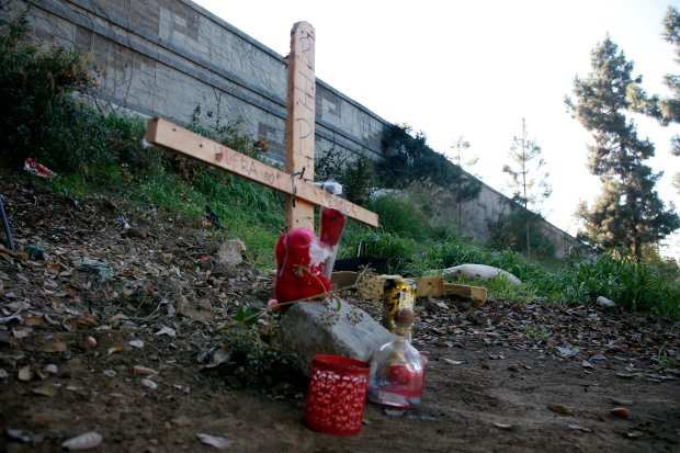 A cross and candle marks the campsite where a woman was found dead yesterday at a homeless camp next to Interstate 280 in San Jose, Calif., Thursday, Dec. 29, 2016. (Karl Mondon/Bay Area News Group)